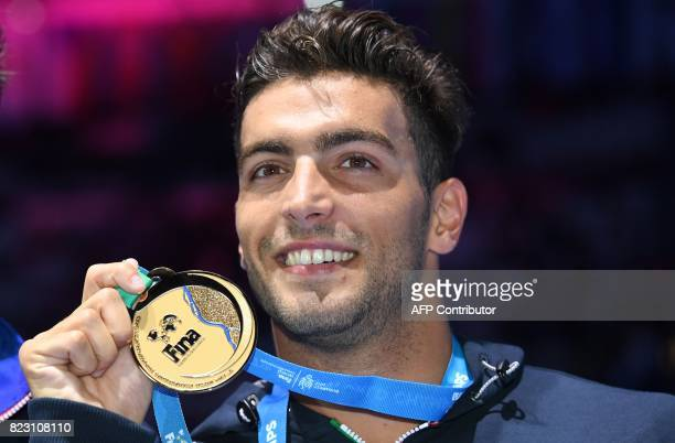 Italy's Gabriele Detti poses with his gold medal during the podium ceremony for the men's 800m freestyle final during the swimming competition at the...