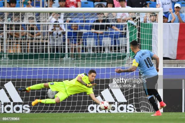 Italy's goalkeeper Alessandro Plizzari saves a penalty shot from Uruguay's forward Rodrigo Amaral during the U20 World Cup third place playoff...