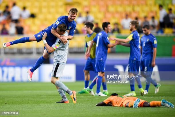 Italy's goalkeeper Andrea Zaccagno lifts up forward Luca Vido as they celebrate their victory during the U20 World Cup quarterfinal football match...