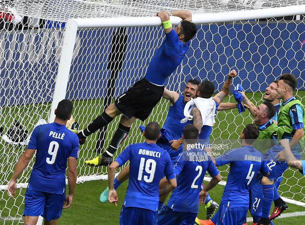 Italy's goalkeeper Gianluigi Buffon (top) climbs to the goal's crossbar as they celebrate at the end of the Euro 2016 round of 16 football match between Italy and Spain at the Stade de France stadium in Saint-Denis, near Paris, on June 27, 2016. / AFP / MIGUEL