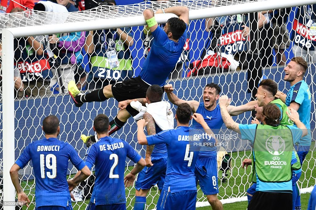 Italy's goalkeeper Gianluigi Buffon (top) climbs to the goal's crossbar as they celebrate at the end of the Euro 2016 round of 16 football match between Italy and Spain at the Stade de France stadium in Saint-Denis, near Paris, on June 27, 2016. / AFP / PHILIPPE