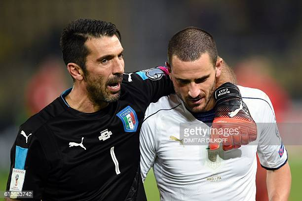 Italy's goalkeeper Gianluigi Buffon speaks with Italy's defender Leonardo Bonucci as they celebrate after winning the FIFA World Cup 2018 qualifying...