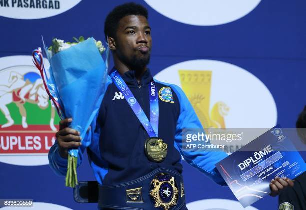 Italy's gold medallist Frank Chamizo poses on the podium during the medal ceremony for the men's freestyle wrestling 70kg category at the FILA World...
