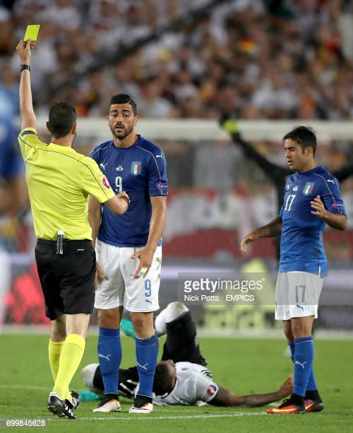 Italy's Graziano Pelle is shown the yellow card by referee Viktor Kassai after a foul on Germany's Jerome Boateng