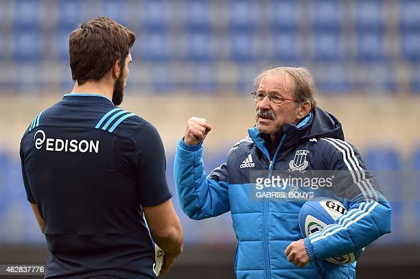 Italy's head coach Jacques Brunel of France speaks speaks to a player during the captain's run of his team on February 6 2015 at the Olympic Stadium...
