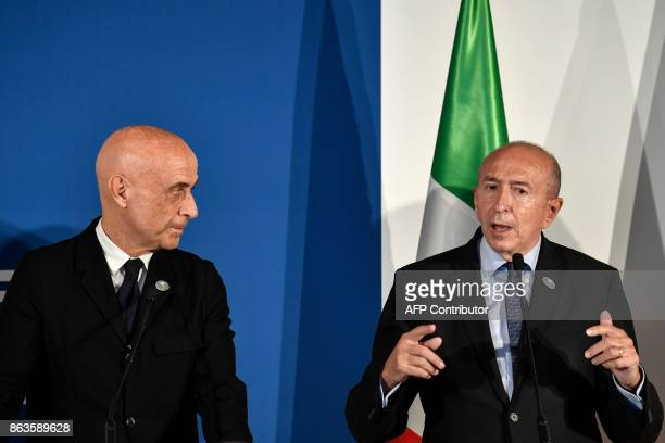 Italy's Interior Minister Marco Minniti looks at France's Interior Minister Gerard Collomb speaking during a press conference at the end of the G7...