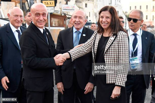Italy's Interior Minister Marco Minniti shakes hands with US Acting Secretary of the Department of Homeland security Elaine Duke as France's Interior...