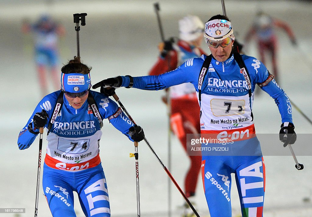 Italy's Karin Oberhofer (L) hand-over with teammate Michela Ponza during the Women 4x6km relay event of the IBU Biathlon World Championships in Nove Mesto, Czech Republic, on February 15, 2013. Norway's won the event ahead of Ukraine (2nd) and Italian (3rd). AFP PHOTO / ALBERTO PIZZOLI