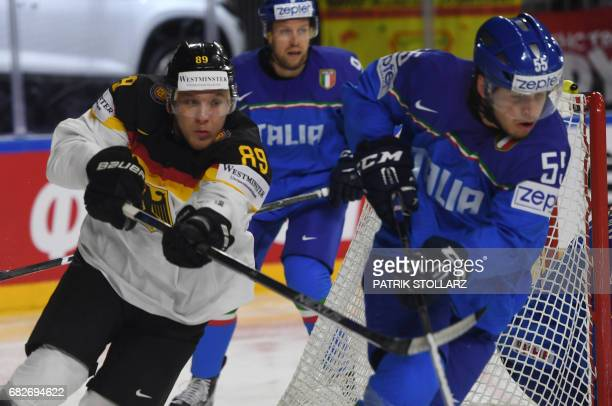 Italy´s Luca Zanatta and Germany´s David Wolf vie during the IIHF Men's World Championship ice hockey match between Italy and Germany in Cologne...