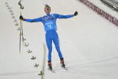 Italy's Lukas Hofer celebrates as he crosses the finish line to snatch bronze in the Biathlon mixed 2x6 km 2x75 km Relay at the Laura CrossCountry...