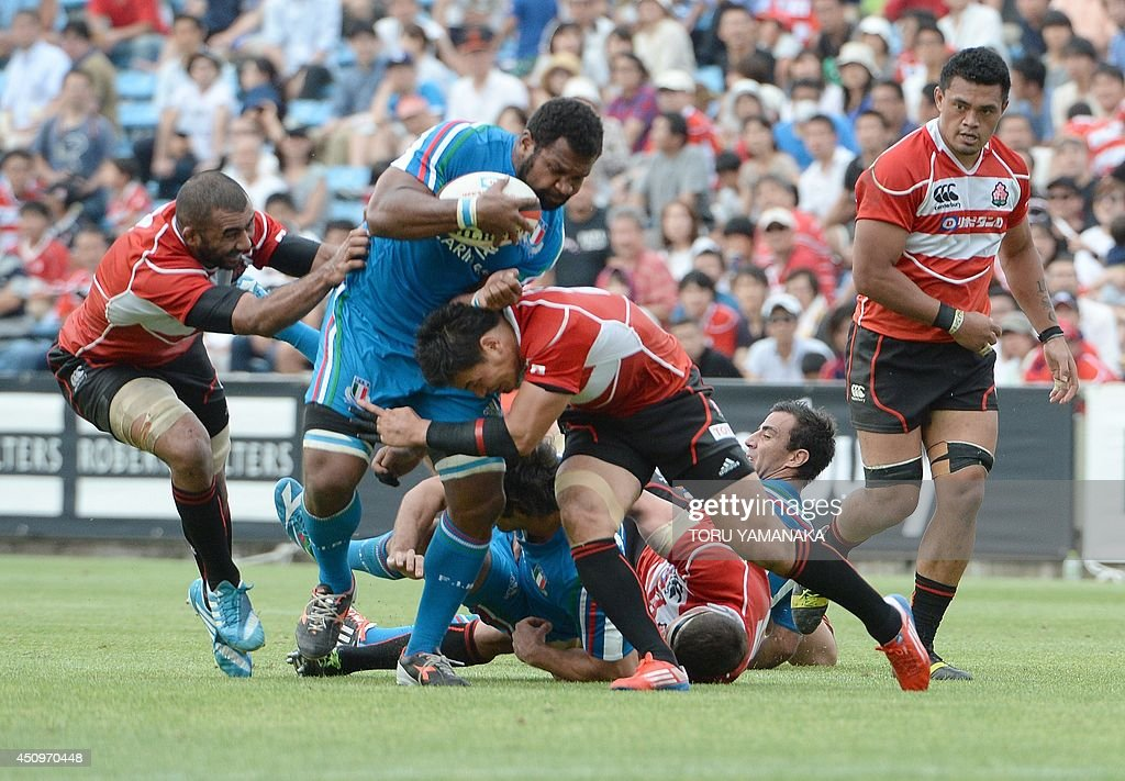 Italy's Manoa Vosawai (2nd L) is tackled by Japan's full-back Ayumu Goromaru (2nd R) and captain Michael Lieitch (L) during a friendly rugby union match in Tokyo on June 21, 2014. Japan defeated Italy 26-23. AFP PHOTO/Toru YAMANAKA