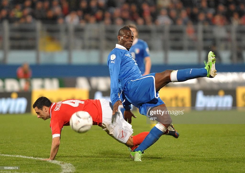 Italy's Mario Balotelli (R) fights for the ball with Malta's Gareth Sciberras during their World Cup Qualifier football match at the National Stadium in Malta on March 26, 2013.