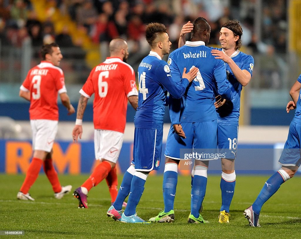 Italy's Mario Balotelli (R) is congratulated by team mates Riccardo Montolivo (R) and Stephen El Shaarawy (left) during the FIFA 2014 World Cup qualifying football match Malta vs.Italy at the National Stadium in Malta on March 26, 2013. AFP PHOTO / MATTHEW MIRABELLI