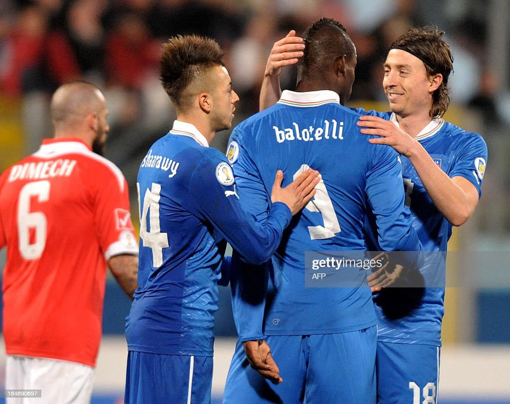 Italy's Mario Balotelli (C) is congratulated by team mates Riccardo Montolivo (R) and Stephen El Shaarawy (left) during the FIFA 2014 World Cup qualifying football match Malta vs.Italy at the National Stadium in Malta on March 26, 2013. AFP PHOTO / MATTHEW MIRABELLI