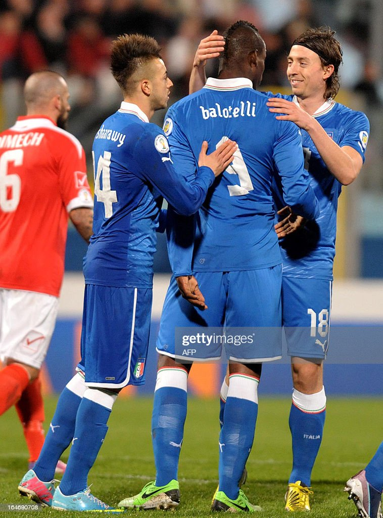 Italy's Mario Balotelli (C) is congratulated by team mates Riccardo Montolivo (R) and Stephen El Shaarawy (left) during the FIFA 2014 World Cup qualifying football match Malta vs.Italy at the National Stadium in Malta on March 26, 2013.