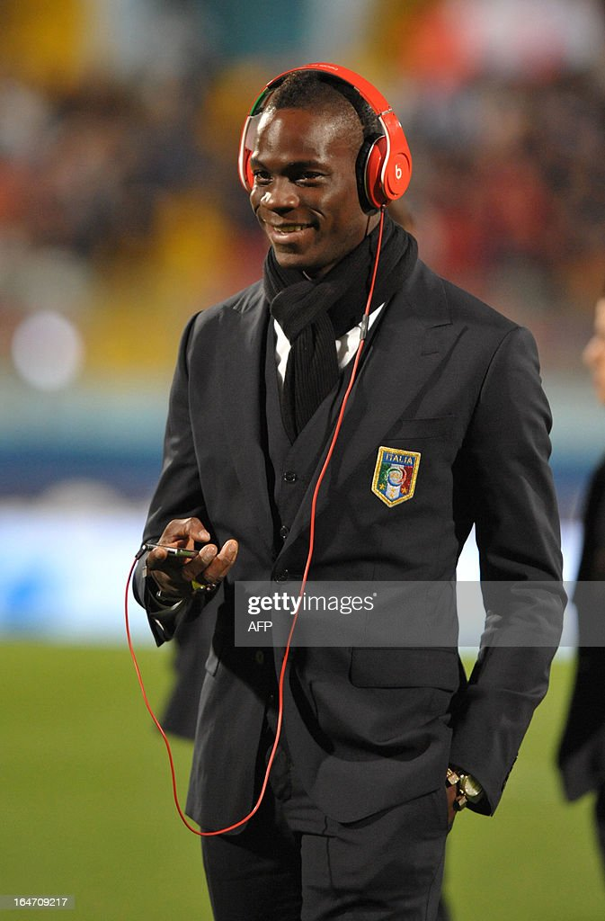 Italy's Mario Balotelli listens to music as he walks on the field before the FIFA 2014 World Cup qualifying football match Malta vs.Italy at the National Stadium in Malta on March 26, 2013.