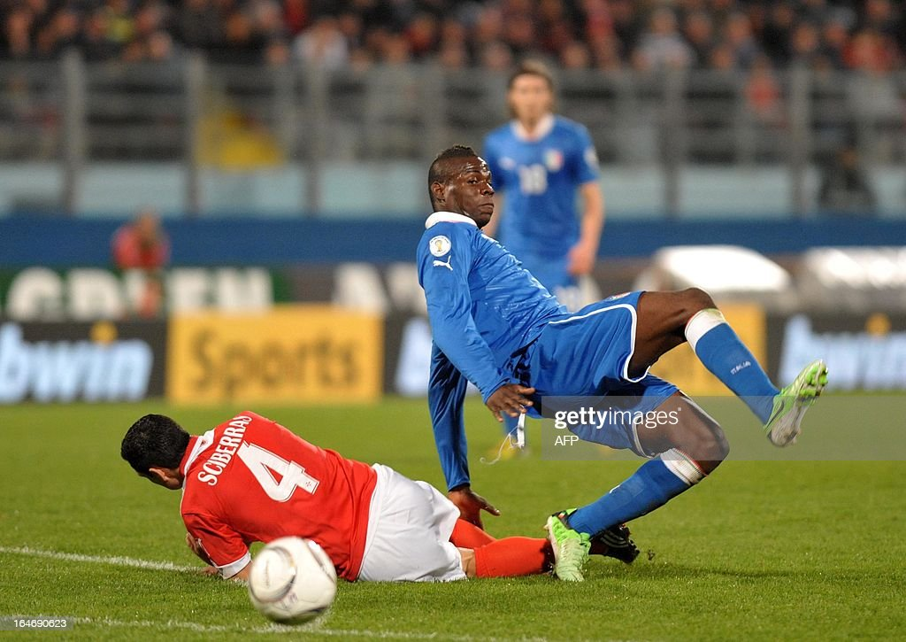 Italy's Mario Balotelli (R) makes vies with Malta's Luke Dimech during the FIFA 2014 World Cup qualifying football match Malta vs.Italy at the National Stadium in Malta on March 26, 2013.