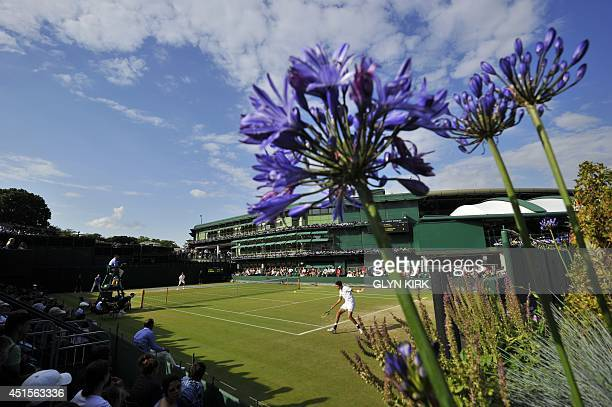 Italy's Matteo Berrettini returns against Russia's Andrey Rublev during their boy's singles second round match on day eight of the 2014 Wimbledon...
