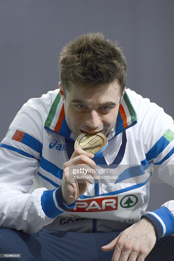Italy's Michael Tumi bites his bronze medal on the podium after the men's 60m final at the European Indoor athletics Championships in Gothenburg, Sweden, on March 2, 2013. AFP PHOTO / JONATHAN NACKSTRAND