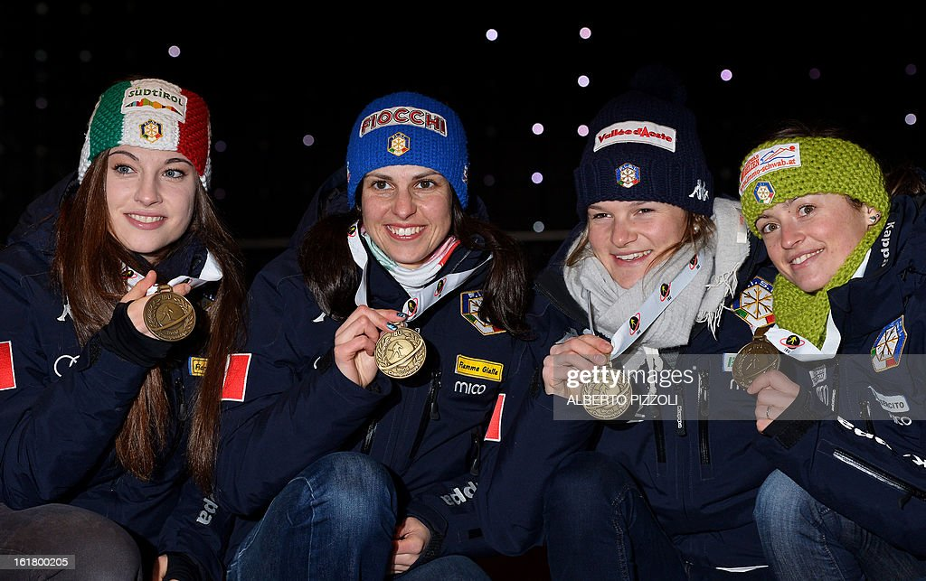 Italy's Michela Ponza, Karin Oberhofer, Nicole Gontier and Dorothea Wierer celebrate their bronze medals for the women 4x6 Km relay as part of IBU Biathlon World Championships in Nove Mesto, Czech Republic, on February 16, 2013. AFP PHOTO / ALBERTO PIZZOLI