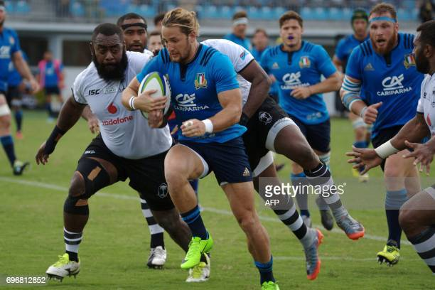 Italy's Michele Campagnaro runs with the ball during their international rugby test match between Fiji and Italy in Suva on June 17 2017 Fiji...