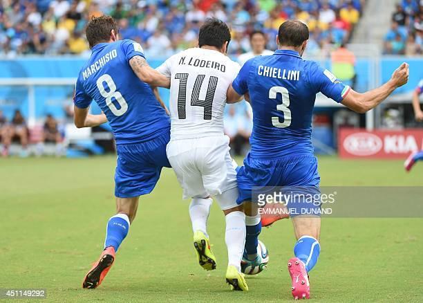 Italy's midfielder Claudio Marchisio and Italy's defender Giorgio Chiellini pressure Uruguay's midfielder Nicolas Lodeiro during the Group D football...
