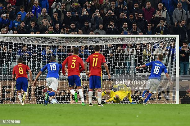 Italy's midfielder Daniele De Rossi kicks and scores a penalty against Spain's goalkeeper David de Gea during the WC 2018 football qualification...