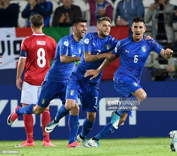 Italy's midfielder Lorenzo Pellegrini celebrates scoring the opening goal with his teammates forward Domenico Berardi and midfielder Marco Benassi...