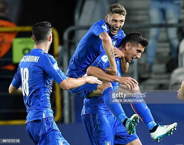 Italy's midfielder Lorenzo Pellegrini celebrates scoring the opening goal with his teammates forward Domenico Berardi and midfielder Roberto...