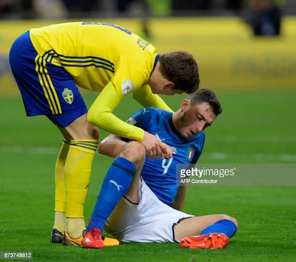 Italy's midfielder Matteo Darmian is helped by Sweden's defender Victor Lindeloef during the FIFA World Cup 2018 qualification football match between...