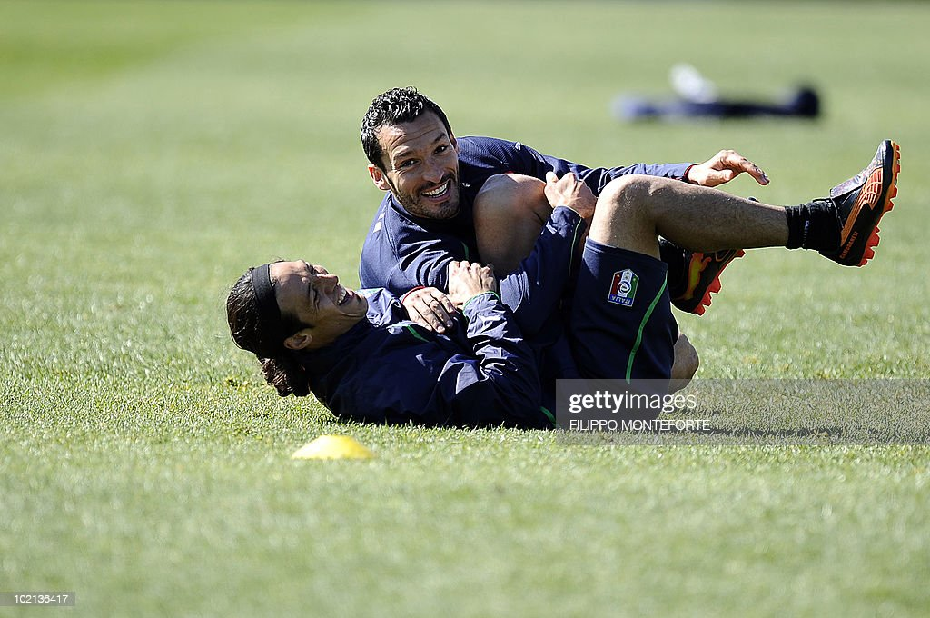 Italy's midfielder Mauro Camoranesi (bottom) and defender Gianluca Zambrotta joke during a training session at Irene's Southdowns College, south of Pretoria on June 16, 2010. Coach Marcello Lippi was calm and confident on June 15 despite reigning champions Italy's failure to win their opening match of the 2010 Football World Cup.
