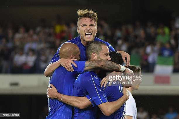 Italy's midfieldrer Antonio Candreva celebrates with teammates Italy's forward Ciro immobile and Leonardo Bonucci after scoring a penalty kick during...