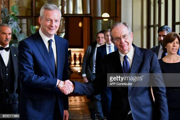 Italy's Minister of the Economy and Finance Pier Carlo Padoan shakes hands with his French counterpart Bruno Le Maire in Rome on August 1 2017 France...