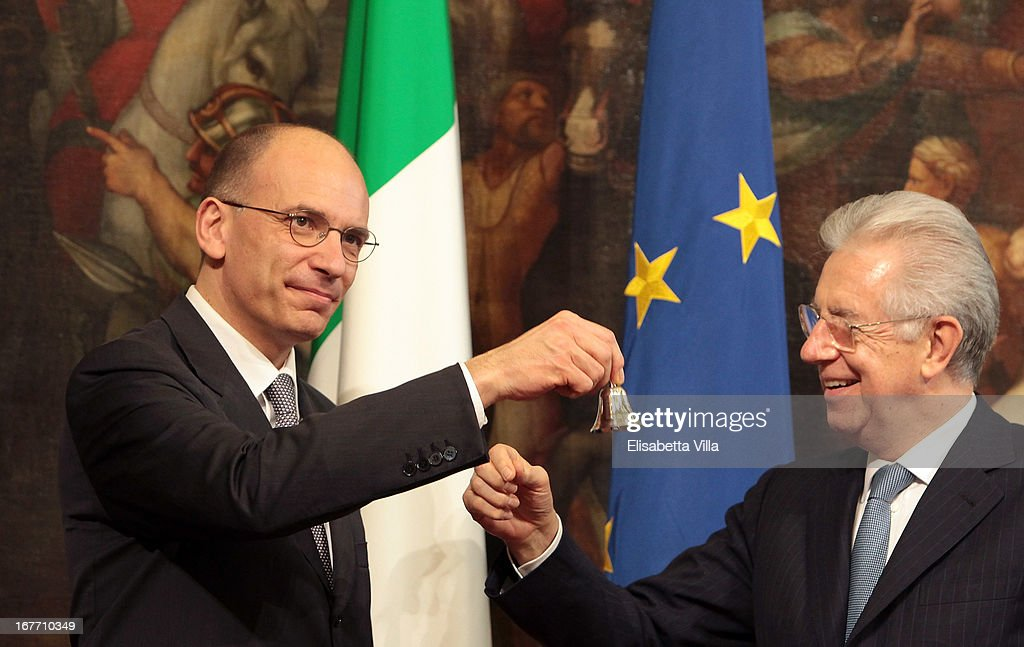 Italy's new Prime Minister Enrico Letta (L) rings the bell which he received from outgoing Prime Minister Mario Monti (R) marking the moment he takes office of the Prime Ministry at Palazzo Chigi on April 28, 2013 in Rome, Italy. The new coalition government was formed through extensive cooperation agreements between the right and left coalitions after a two-month long post-election deadlock.