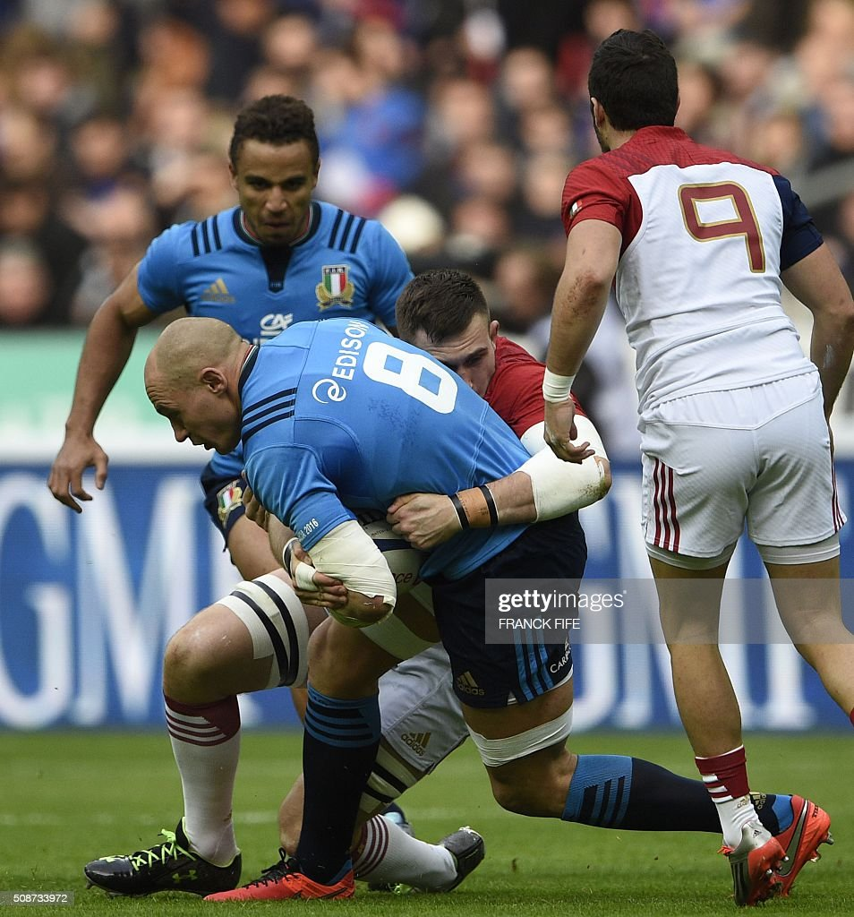 Italy's number 8 and captain Sergio Parisse (L) is tackled by France's lock Paul Jedrasiak (C) during the Six Nations international rugby union match between France and Italy at the Stade de France in Saint-Denis, north of Paris, on February 6, 2016. AFP PHOTO / FRANCK FIFE / AFP / FRANCK FIFE