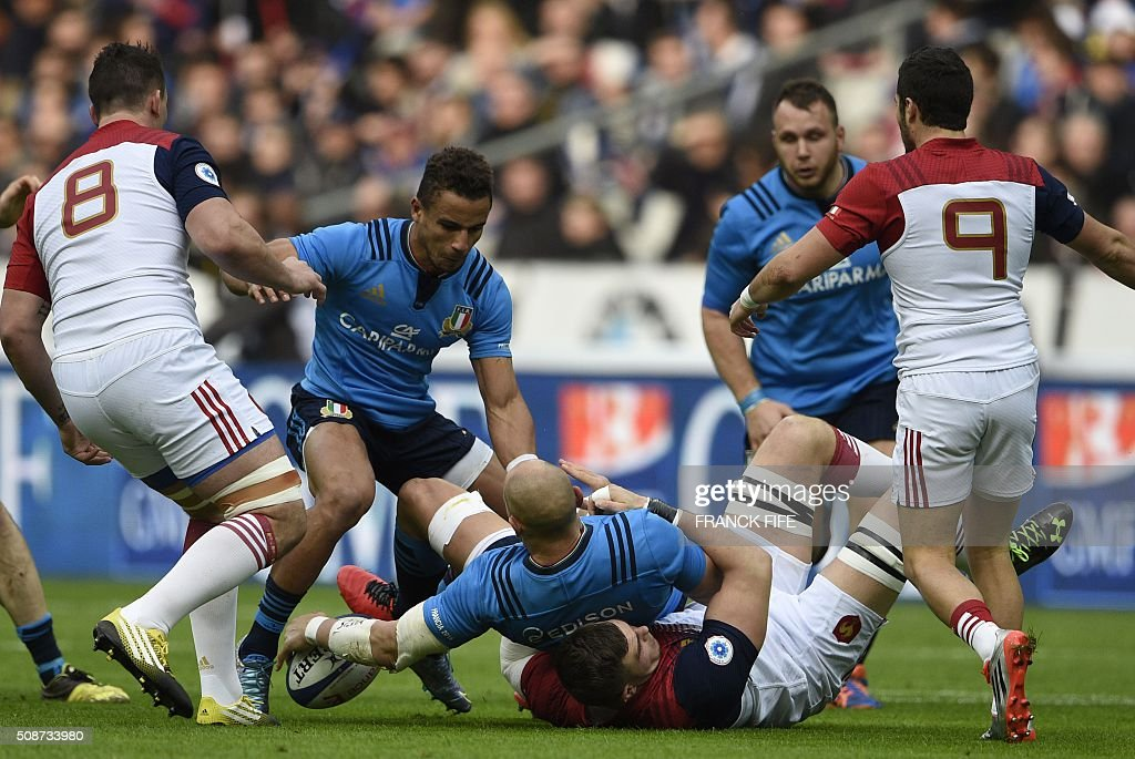 Italy's number 8 and captain Sergio Parisse (C-L) is tackled by France's lock Paul Jedrasiak (C-R) during the Six Nations international rugby union match between France and Italy at the Stade de France in Saint-Denis, north of Paris, on February 6, 2016. AFP PHOTO / FRANCK FIFE / AFP / FRANCK FIFE