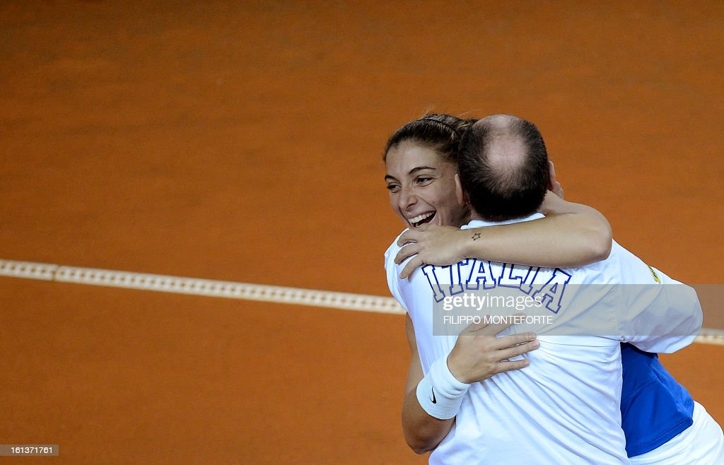 Italy's player Sara Errani (L) embraces coach Corrado Barazutti after winning with teammate Roberta Vinci against US players Liezel Huber and Varvara Lepchenko during their Fed Cup tennis match in Rimini's 105 Stadium on February 10, 2013. The Italians won 6-2, 6-2 as Italy beats USA 3-2 going throught the semifinals.