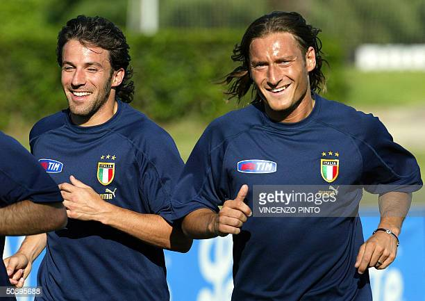 Italy's players Alessandro Del Piero and Francesco Totti smile as they run during a training session at Coverciano training camp near Florence 25 May...