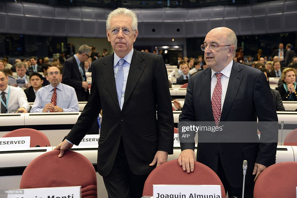 Italy's Prime Minister Mario Monti (L) arrives with European Union Commissioner for Competition Joaquin Almunia, prior to the European Competition Forum held at the EU Commission headquarter in Brussels, on February 28, 2013. AFP PHOTO THIERRY CHARLIER