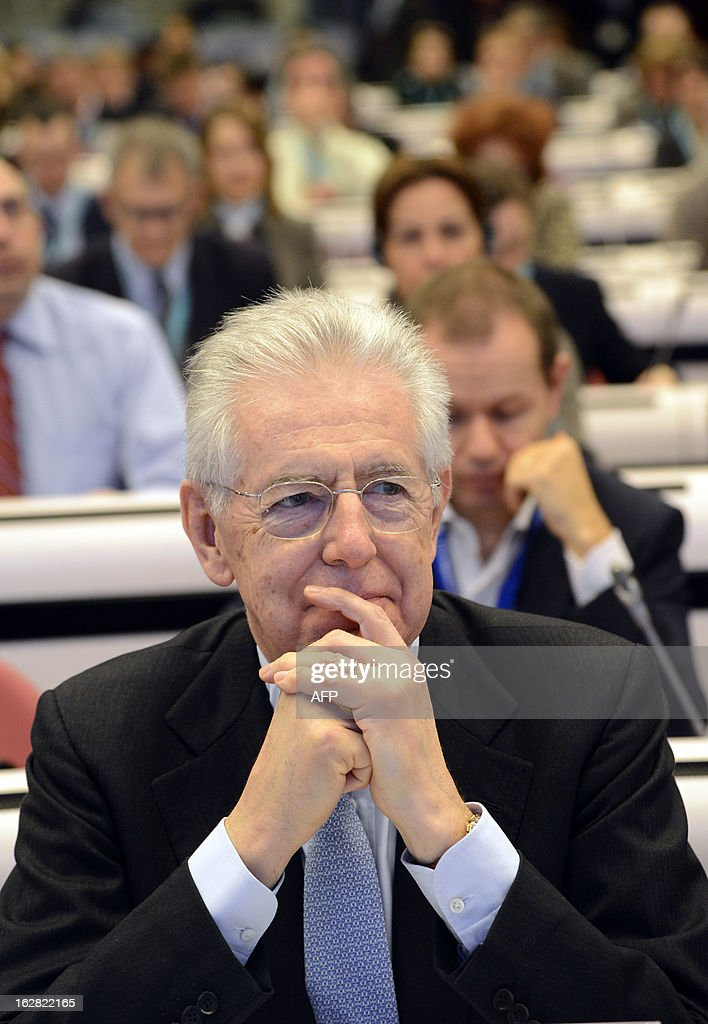 Italy's Prime Minister Mario Monti attends the European Union Commissioner for Competition Joaquin Almunia, during the European Competition Forum held at the EU Commission headquarter in Brussels, on February 28, 2013.