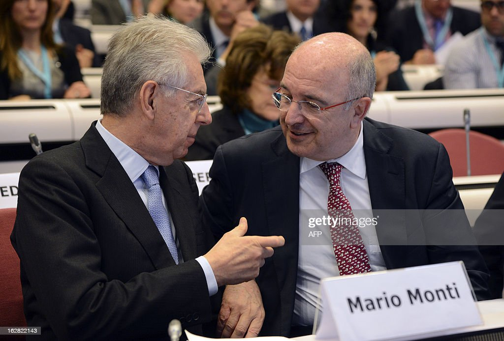 Italy's Prime Minister Mario Monti (L) speaks with European Union Commissioner for Competition Joaquin Almunia, during the European Competition Forum held at the EU Commission headquarter in Brussels, on February 28, 2013.