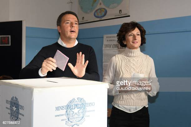 Italy's Prime Minister Matteo Renzi and his wife Agnese Landini vote for a referendum on constitutional reforms on December 4 2016 at a polling...