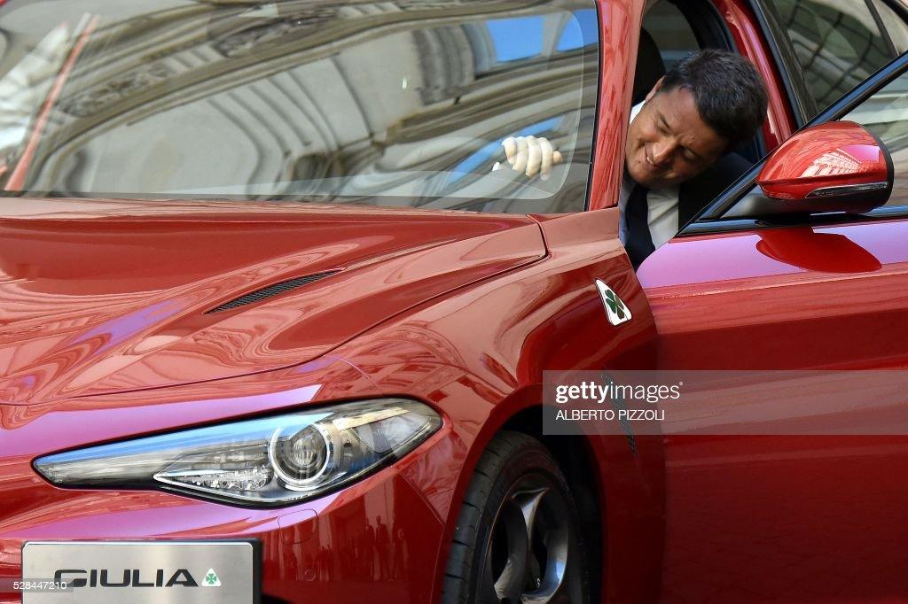 Italy's Prime Minister Matteo Renzi gets into the new FCA (FIAT) car 'Giulia' during the presentation of the car on May 5, 2016 at Chigi palace in Rome. / AFP / ALBERTO