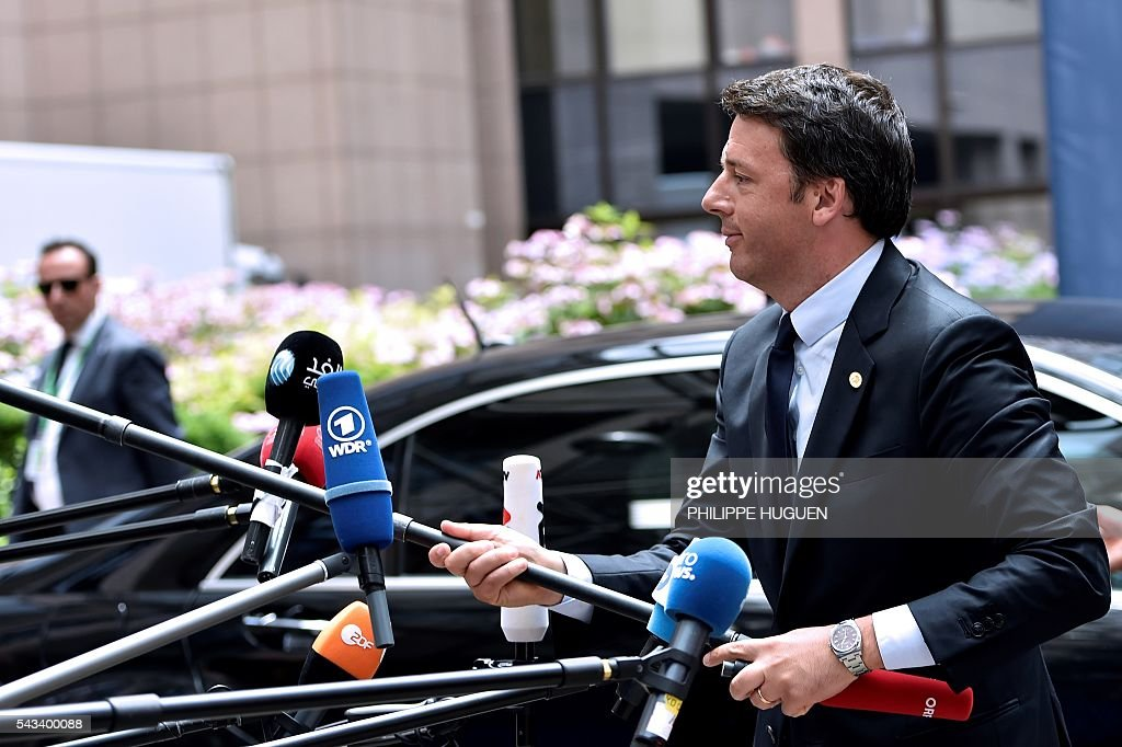 Italy's Prime minister Matteo Renzi grabs a microphone as he arrives before an EU summit meeting on June 28, 2016 at the European Union headquarters in Brussels on June 28, 2016. / AFP / PHILIPPE