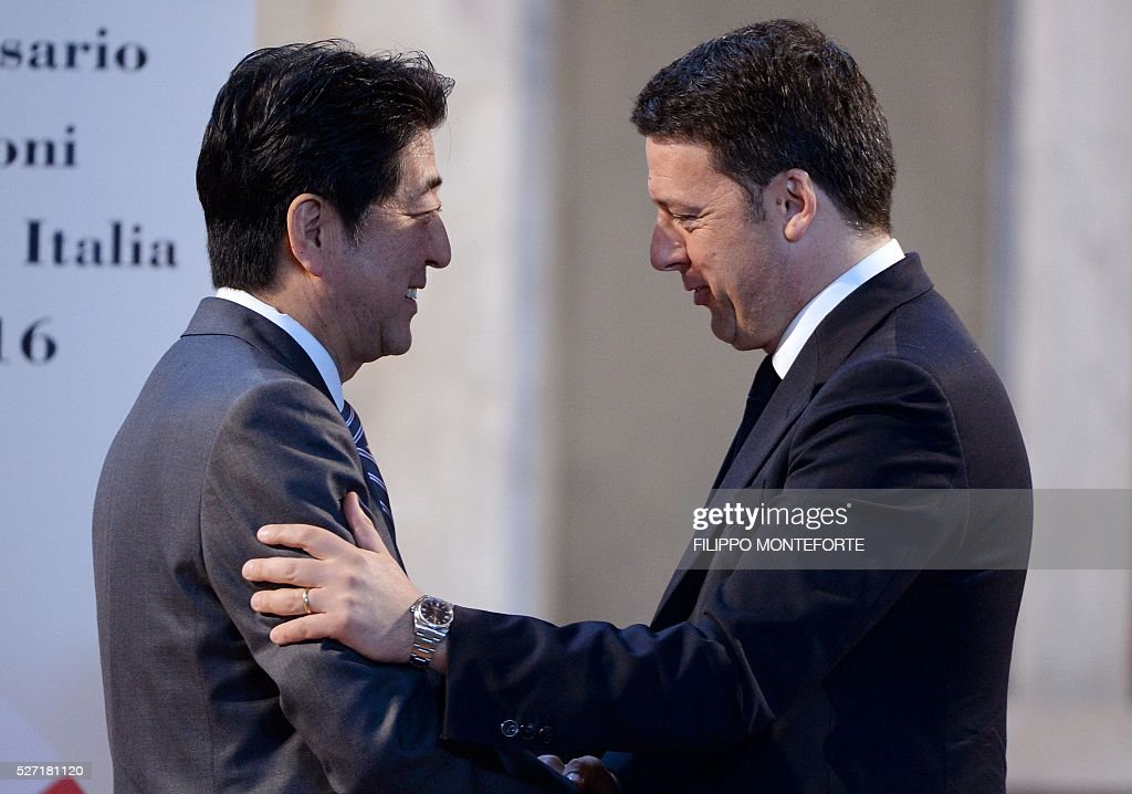 Italy's Prime Minister Matteo Renzi (R) shakes hand with his Japanese counterpart Shinzo Abe after their joint press conference following their meeting at Palazzo Vecchio in Florence on May 2, 2016. / AFP / Filippo MONTEFORTE