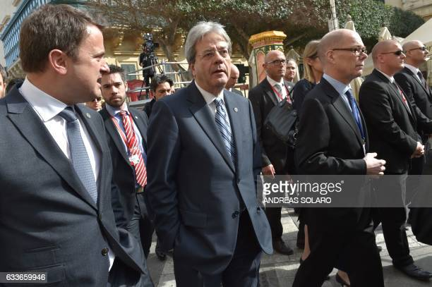 Italy's prime Minister Paolo Gentiloni walks along with Luxembourg's Prime Minister Xavier Bettel before a family picture during an European Union...