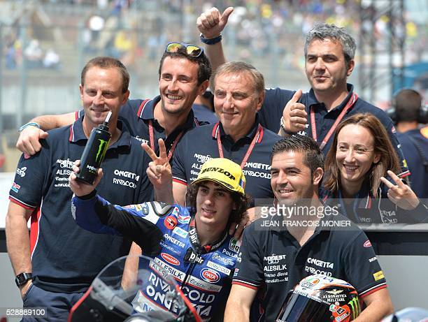Italy's rider Niccolo Antonelli pole celebrates witn team after the Moto3 qualifying cession of the French motorcycling Grand Prix ahead of the...