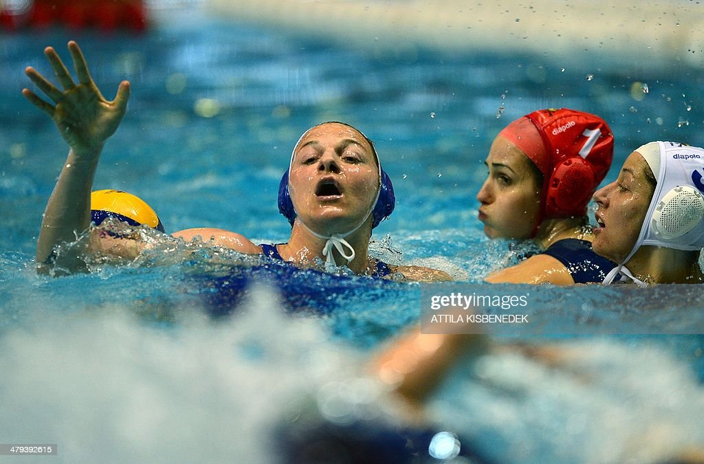 Italy's Roberta Bianconi (L) is pushed down by Hungary's Gabriella Szucs (R) and goalkeeper Orsolya Kaso (C) in the local swimming pool of Budapest on March 18, 2014 during a World League match between their teams. AFP PHOTO / ATTILA KISBENEDEK