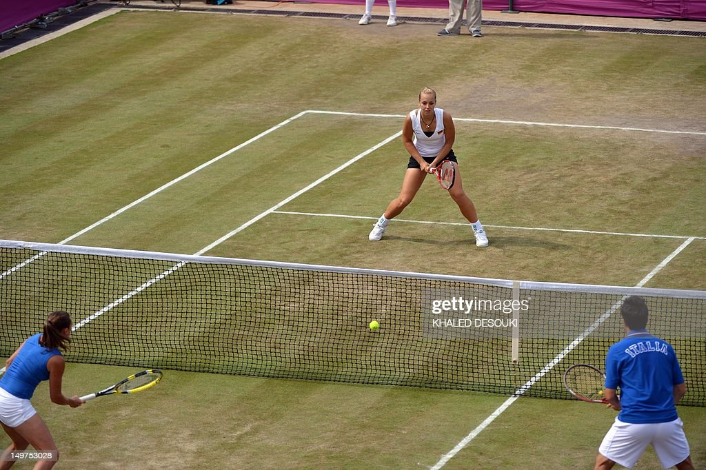 Italy's Roberta Vinci and Daniele Bracciali returns to Germany's Sabine Lisicki (background) and Christopher Kas during their London 2012 Olympic Games mixed double quarter final match at the All England Tennis Club in Wimbledon, southwest London, on August 3, 2012.