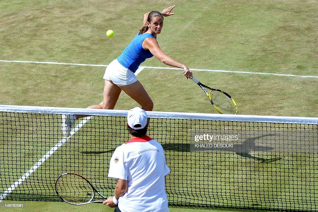 Italy's Roberta Vinci returns to Germany's Christopher Kas and Sabine Lisicki during her London 2012 Olympic Games mixed doubles quarter-final tennis match with teammate Daniele Bracciali at the All England Tennis Club in Wimbledon, southwest London, on August 3, 2012.